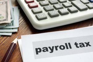 Payroll tax concept. Papers, calculator and money.