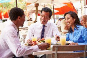 Three Businesspeople Having Meeting In Outdoor Restaurant