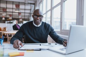 Portrait of confident young man at his desk with laptop doing paperwork. Happy african man looking at camera while at work.